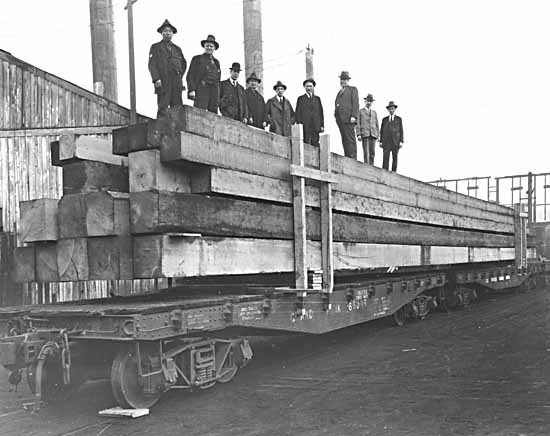 VPL #12443, Leonard Frank, 1925, men standing on lumber on Grand Trunk flatcar at Hastings Mill